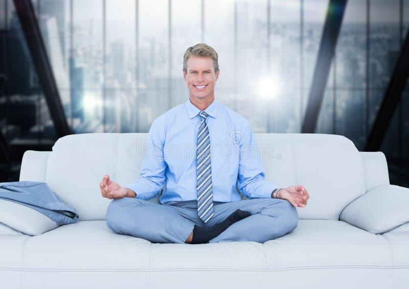 Affärsman som mediterar på soffan mot oskarpt mörker - blått fönster arkivfoto