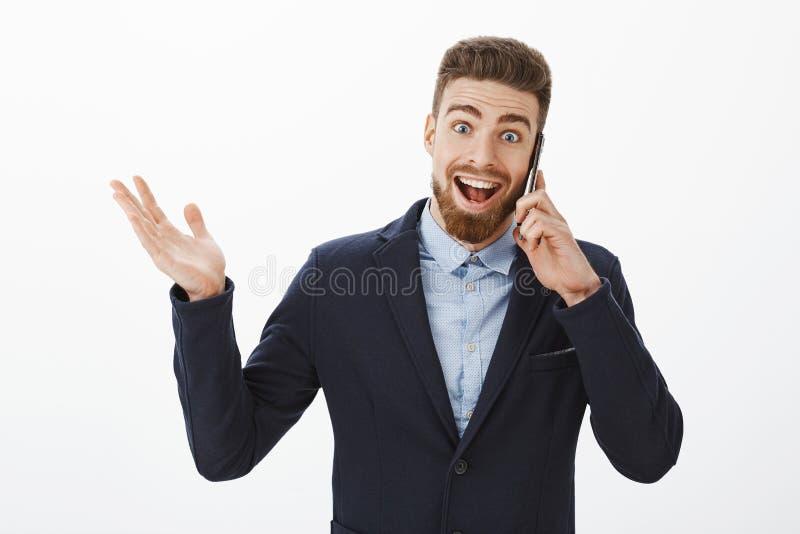 Affärsman som mottar utmärkt nyheterna Lycklig och upphetsad förtjust snygg manlig entreprenör i elegant dräktinnehav royaltyfri foto