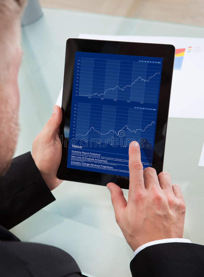 Affärsman som navigerar på hans minnestavla-PC royaltyfri foto