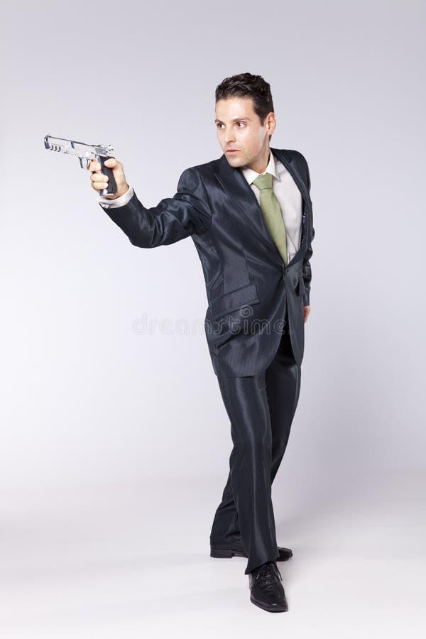 Affärsman som pekar en handeldvapen royaltyfria bilder