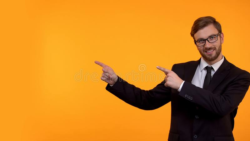 Aff?rsman som pekar fingrar p? gul bakgrund, st?lle f?r din text, mall royaltyfri bild