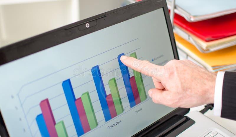 Affärsman som pekar hans finger på en graf fotografering för bildbyråer