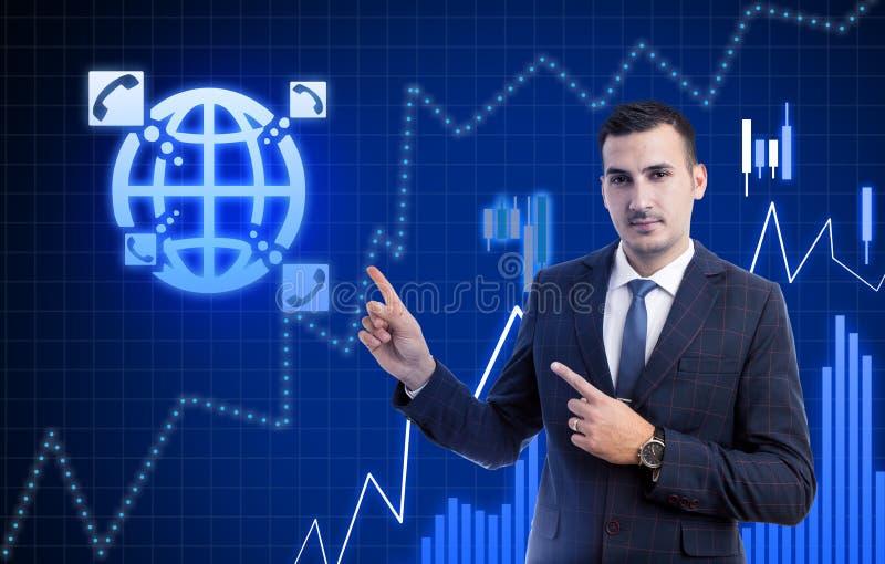 Affärsman som pekar på telefon- och jordklotsymboler arkivbild