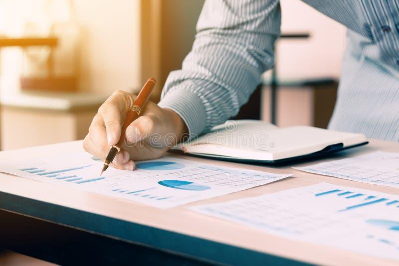 Affärsman som pekar pennan på graf för summarisk rapport för skrivbordsarbetediagram arkivfoto