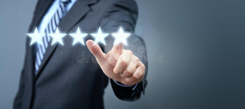 Affärsman som pekar till för servicevärdering för fem stjärna symbolet royaltyfria bilder