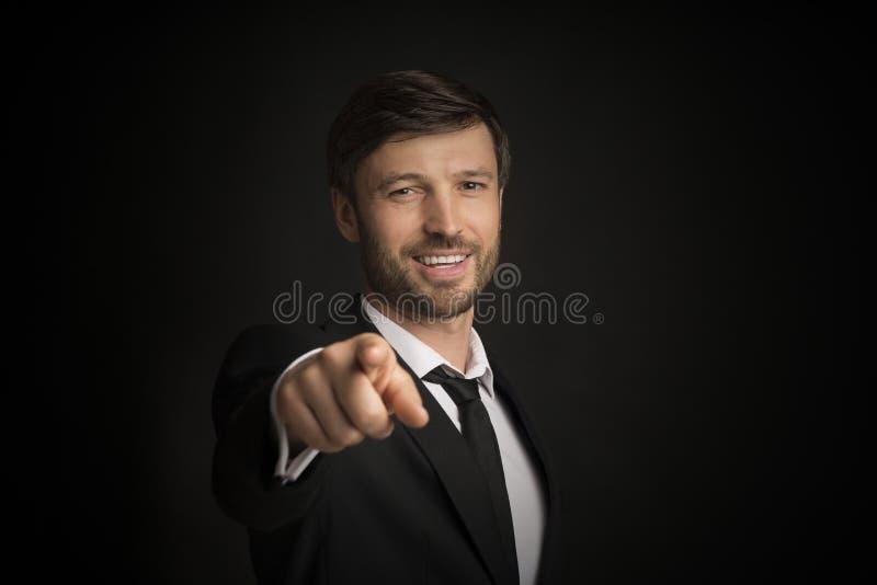Affärsman som pekar ut Finger som ler i Camera, Studio Shot royaltyfria foton