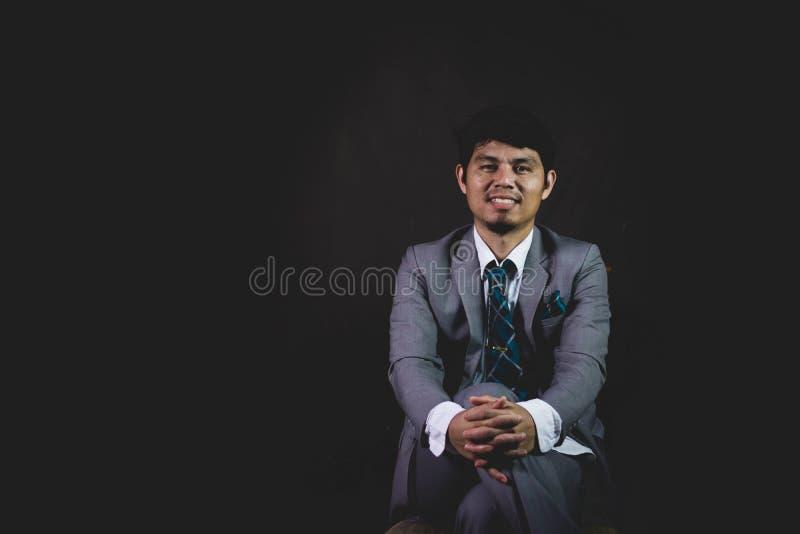 Affärsman som placeras på stol och smilling royaltyfri foto