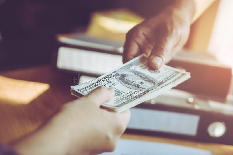 Affärsman som räcker pengar över handla för affär arkivbild
