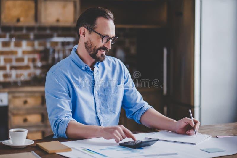 Affärsman som räknar det hemmastadda kontoret för räkningar arkivbild