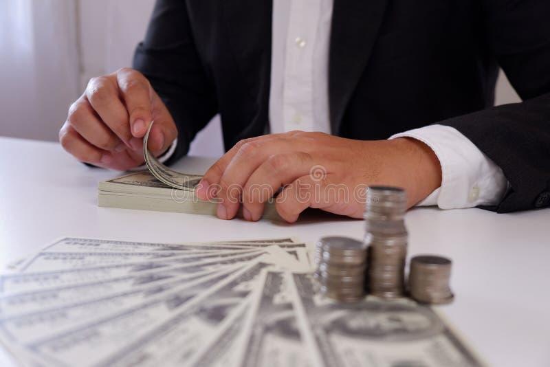 Affärsman som räknar pengar med mynt och pengar över skrivbordet royaltyfria bilder