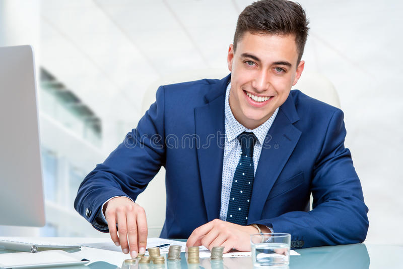 Affärsman som räknar pengar på skrivbordet royaltyfria bilder