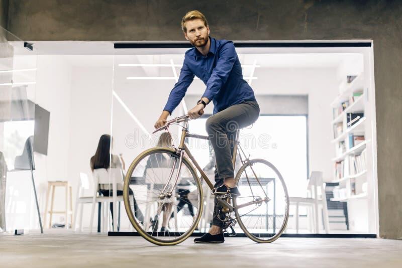 Affärsman som rider en cykel arkivfoto