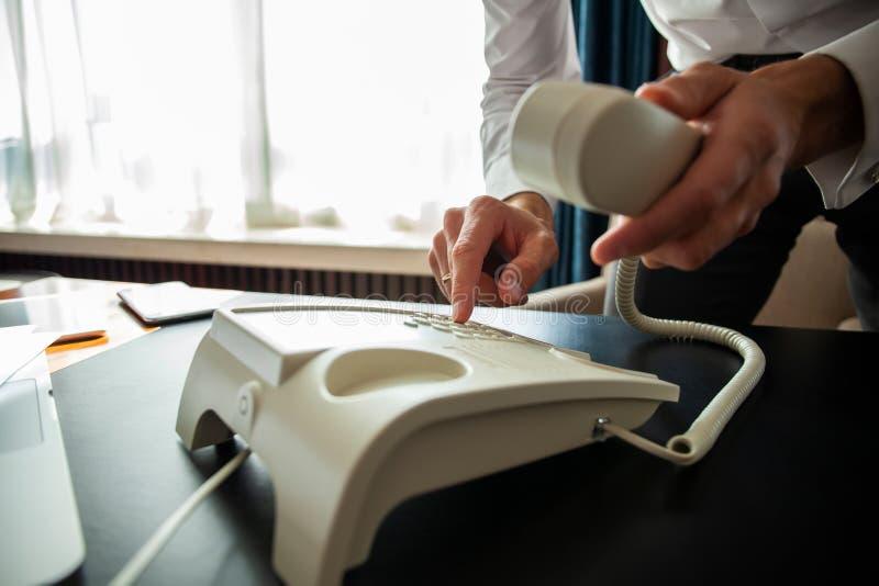 Affärsman som ringer ett telefonnummer för att göra en påringning arkivfoton