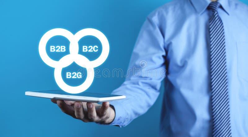 Affärsman som rymmer B2B, B2C, B2G-affärsmodeller Conc affär fotografering för bildbyråer