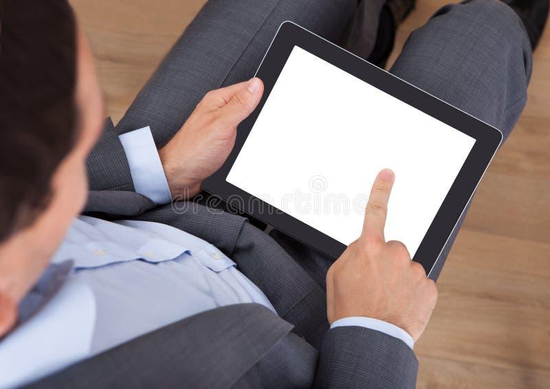 Affärsman som rymmer den digitala tableten royaltyfria foton