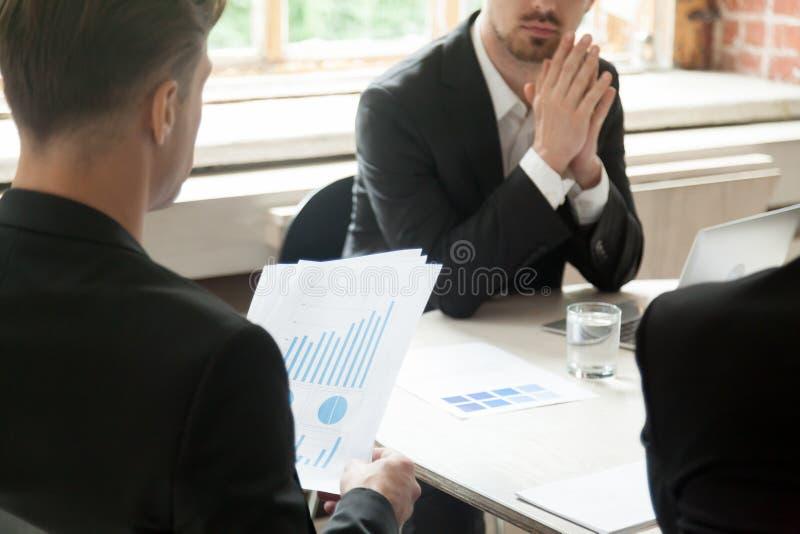 Affärsman som rymmer den finansiella rapporten på möte med partners, c fotografering för bildbyråer