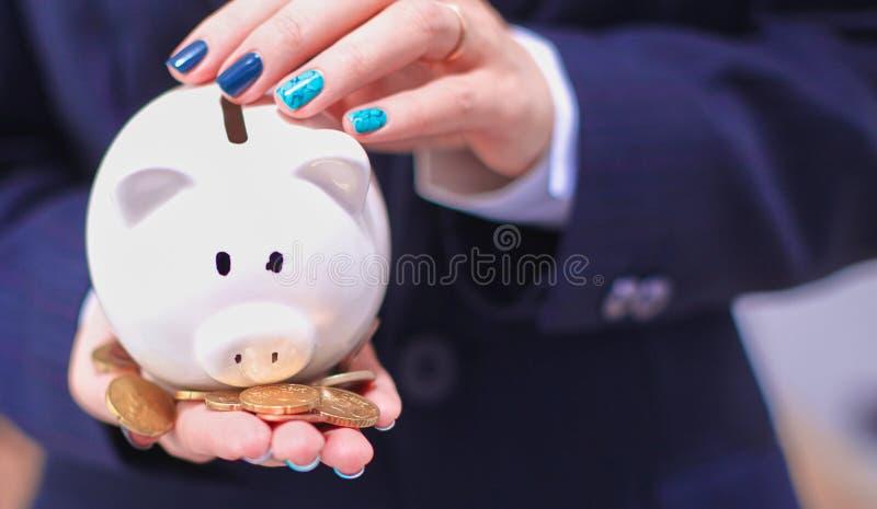 Affärsman som rymmer den piggy asken som i regeringsställning står royaltyfri fotografi