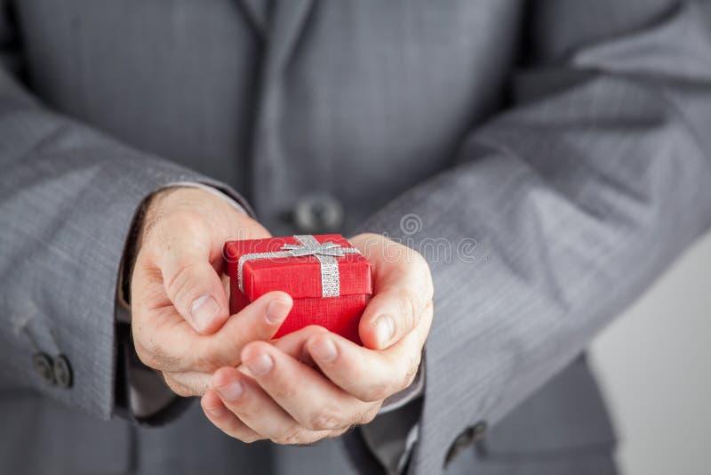 Affärsman som rymmer den röda gåvaasken royaltyfri fotografi