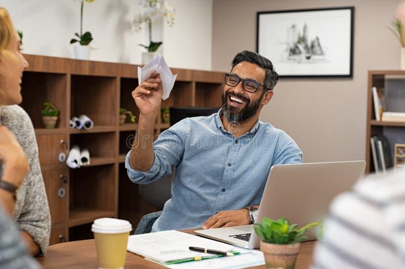 Affärsman som rymmer det pappers- flygplanet på kontoret royaltyfri bild