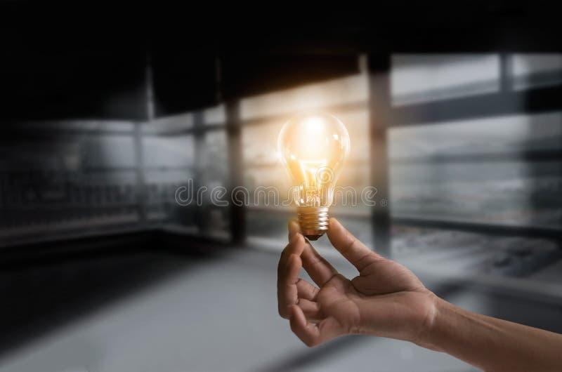 Affärsman som rymmer det upplysta begreppet för ljus kula för idéer för idé-, innovation- och kreativitetinspirationbegrepp arkivfoto