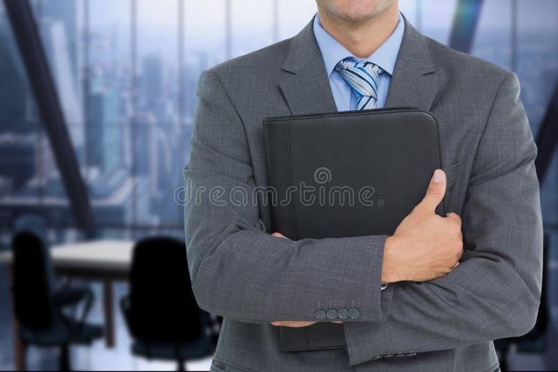 affärsman som rymmer en anteckningsbok mot kontorsbakgrund arkivbilder