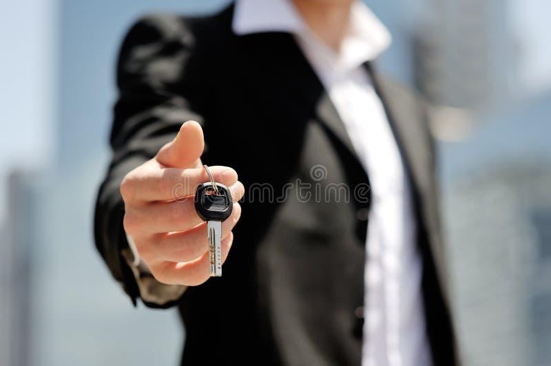 Affärsman som rymmer en biltangent i hans hand - nytt begrepp för bilköpförsäljning royaltyfria foton