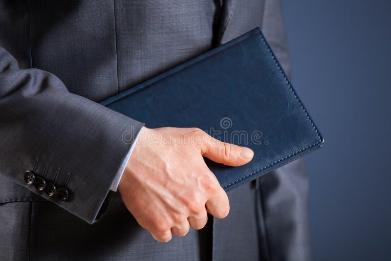 Affärsman som rymmer en bok arkivfoto