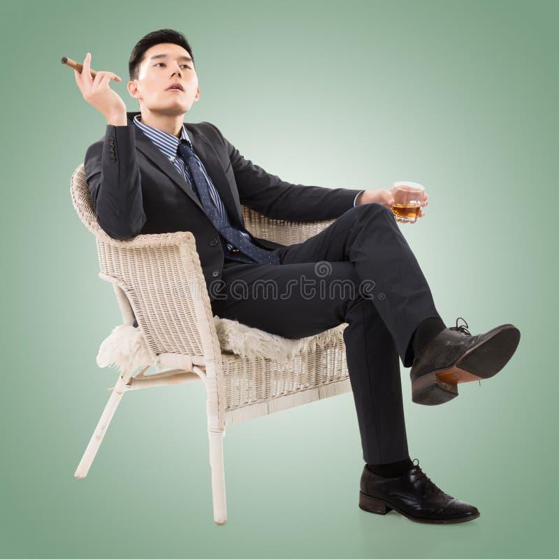 Affärsman som rymmer en cigarr arkivfoto