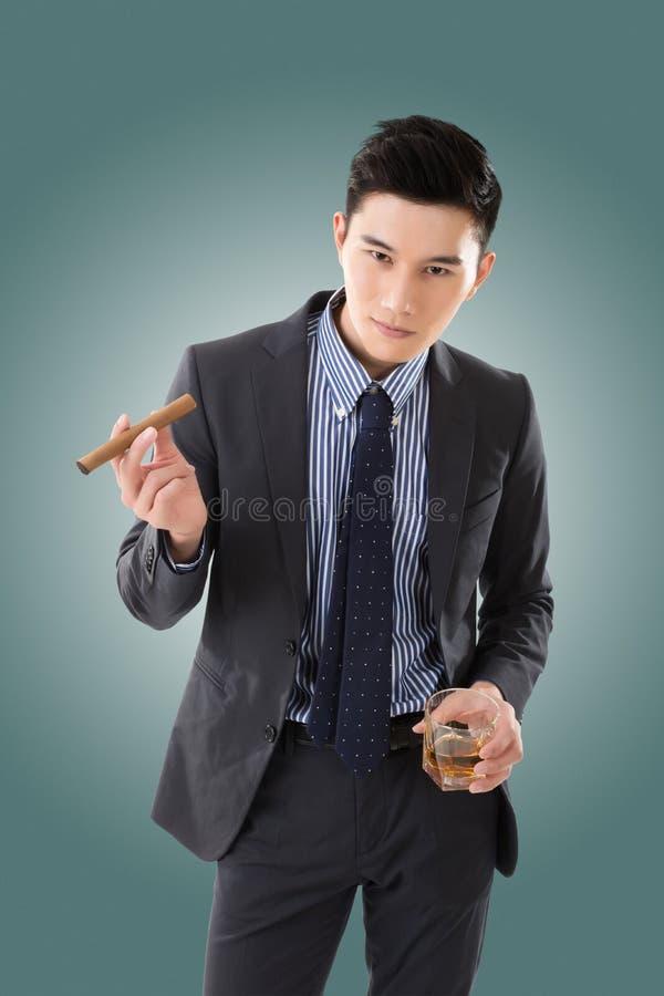 Affärsman som rymmer en cigarr arkivbilder