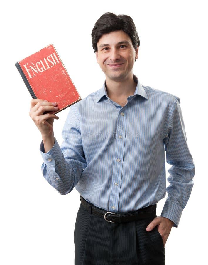 Affärsman som rymmer en engelsk bok arkivfoto