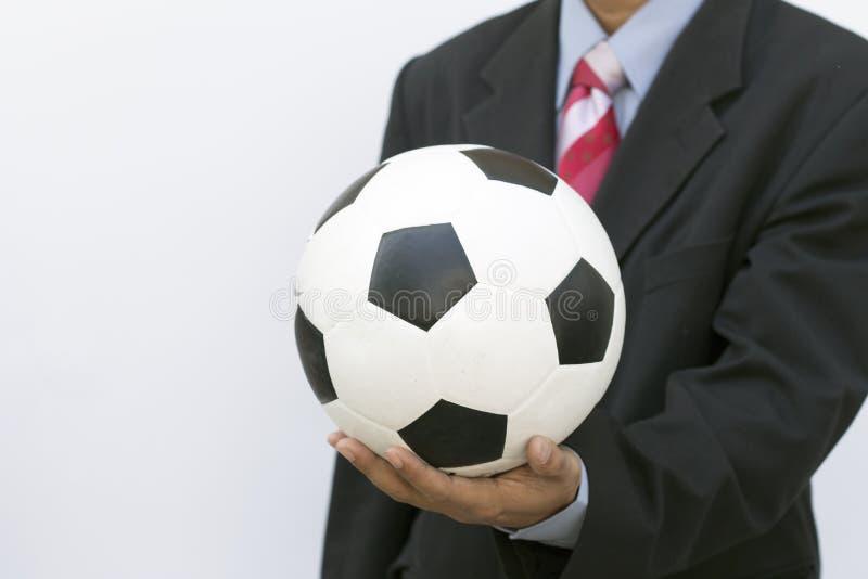Affärsman som rymmer en fotbollboll royaltyfri bild