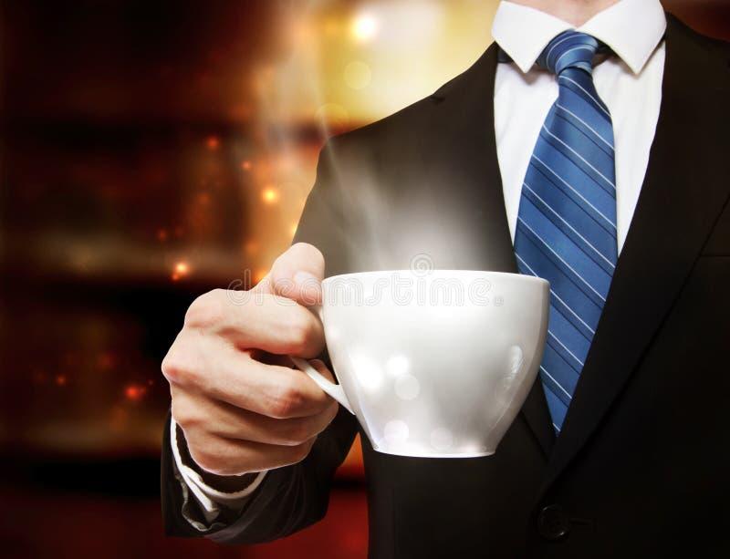 Affärsman som rymmer en kopp kaffe royaltyfri bild