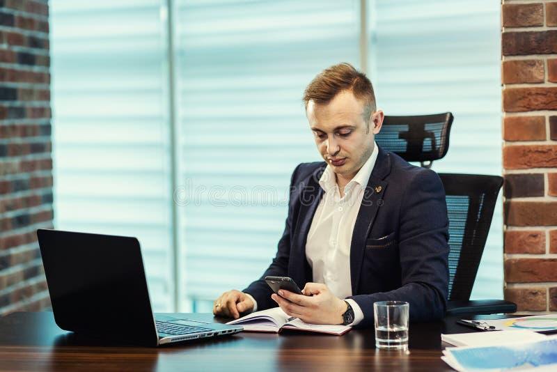 Affärsman som rymmer en mobiltelefon och skriver smsmeddelandet i offi arkivfoton