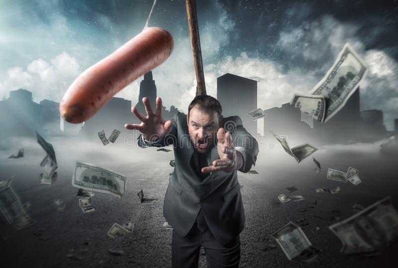 Affärsman som rymmer en morot i en pinne royaltyfri fotografi