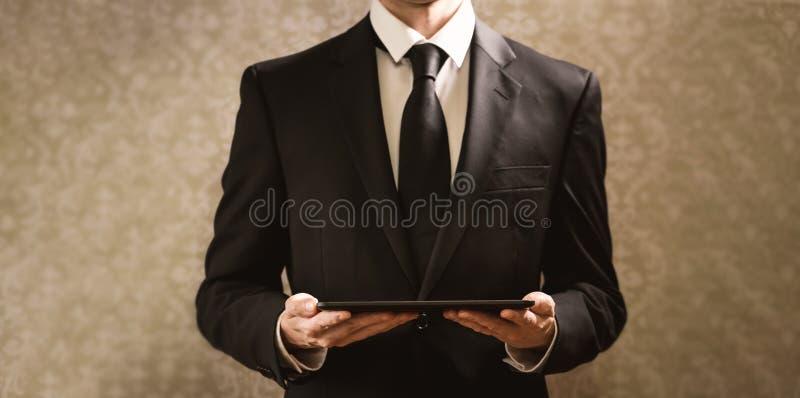 Affärsman som rymmer en tabletdator royaltyfria bilder
