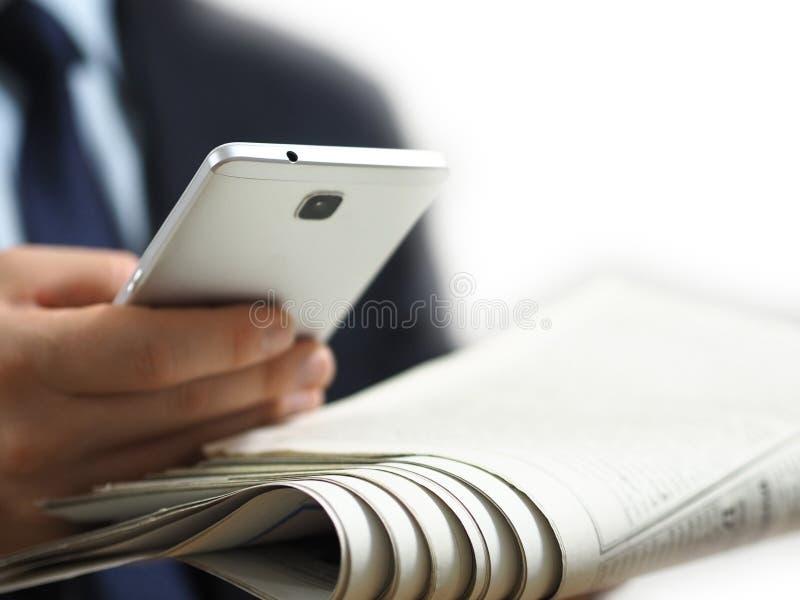 Affärsman som rymmer en tidning och en smart telefon i hans hand Den vita bakgrundsbilden fotografering för bildbyråer