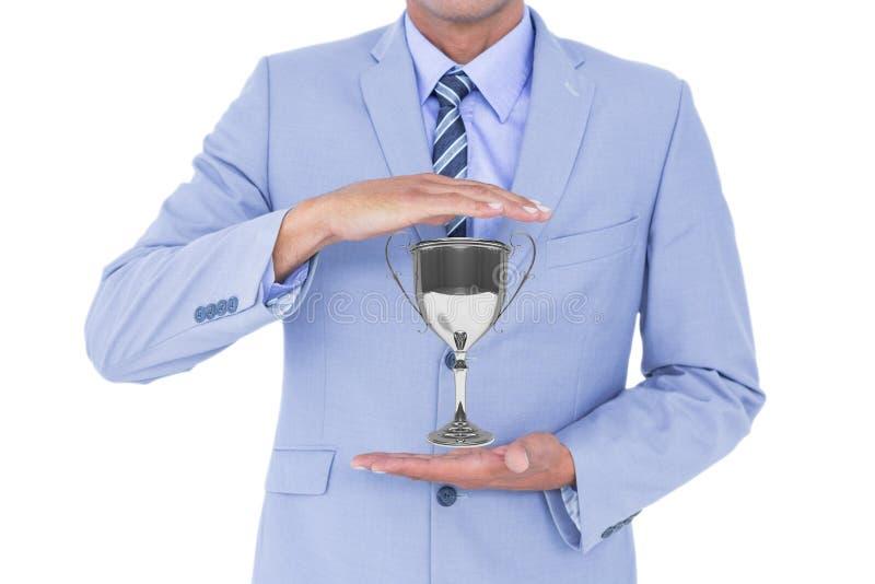 Affärsman som rymmer en trofé i hans händer mot vit bakgrund royaltyfria bilder