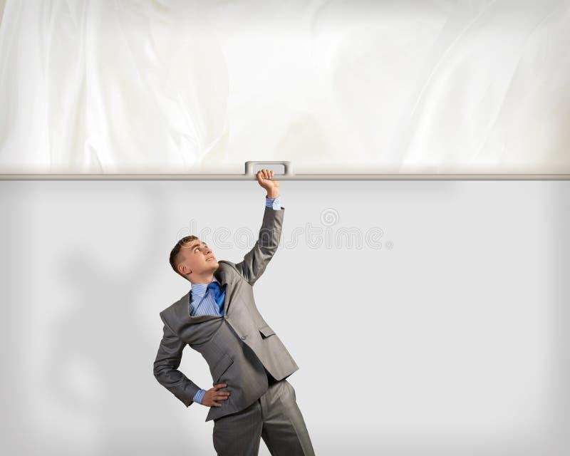 Affärsman som rymmer ett baner med en hand arkivfoton