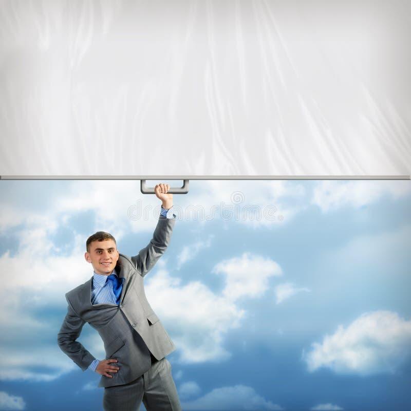 Affärsman som rymmer ett baner med en hand royaltyfri foto