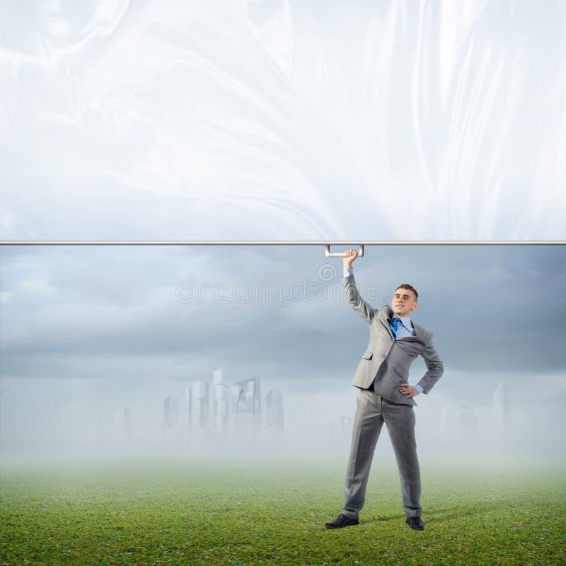 Affärsman som rymmer ett baner med en hand arkivbild
