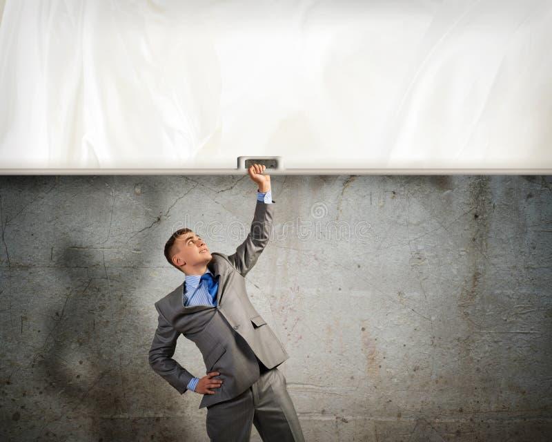 Affärsman som rymmer ett baner med en hand arkivbilder