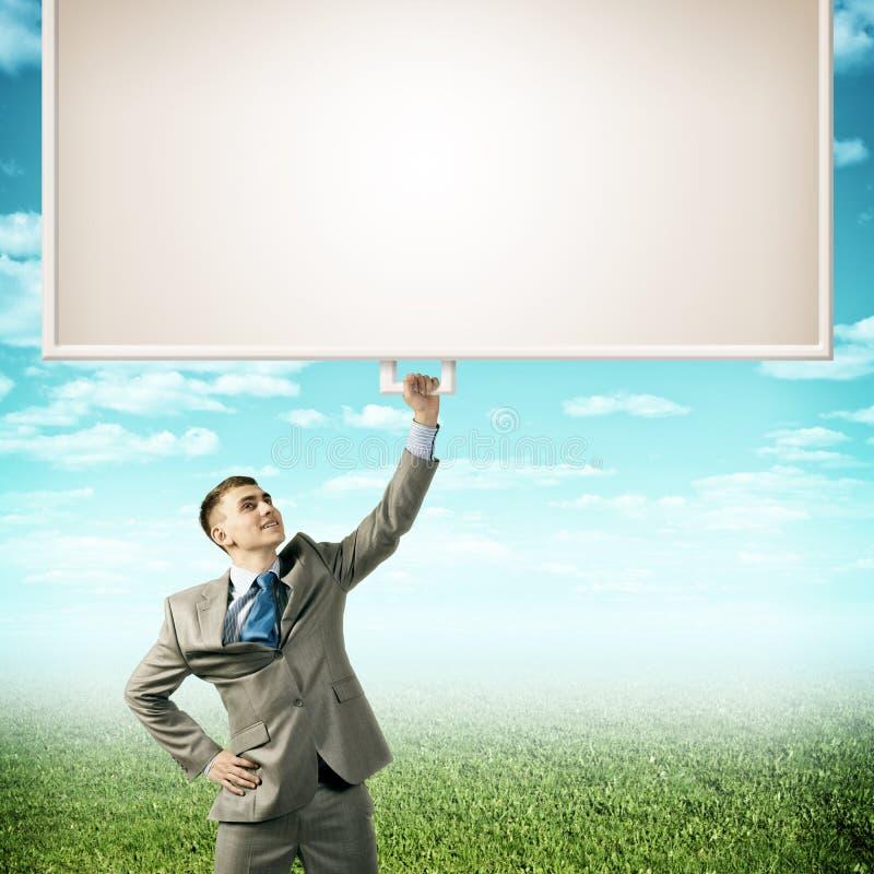 Affärsman som rymmer ett baner med en hand royaltyfria bilder