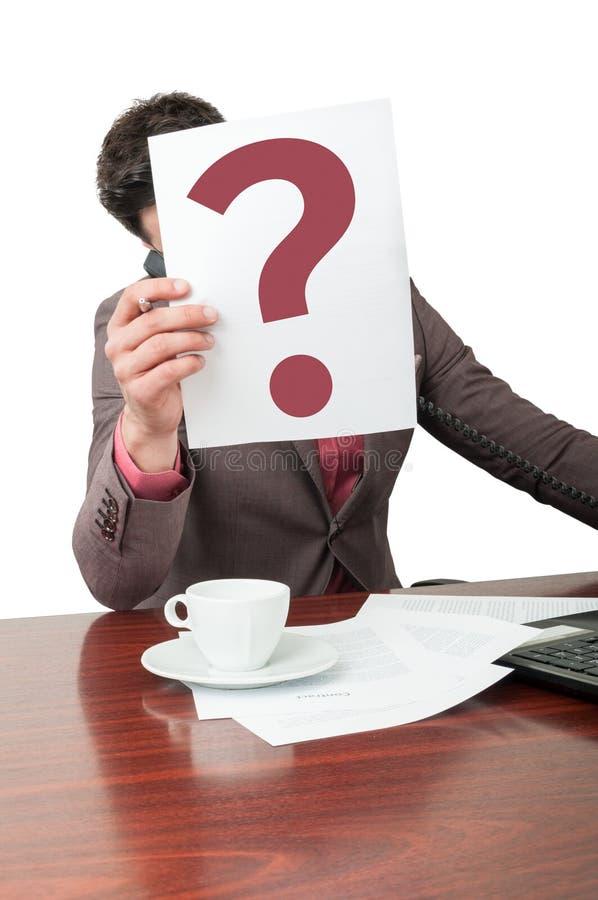 Affärsman som rymmer ett papper med frågefläcken royaltyfri bild