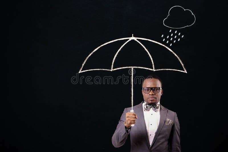 Affärsman som rymmer ett paraply royaltyfri bild