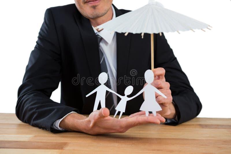 Affärsman som rymmer ett paraply som skyddar en familj royaltyfri bild