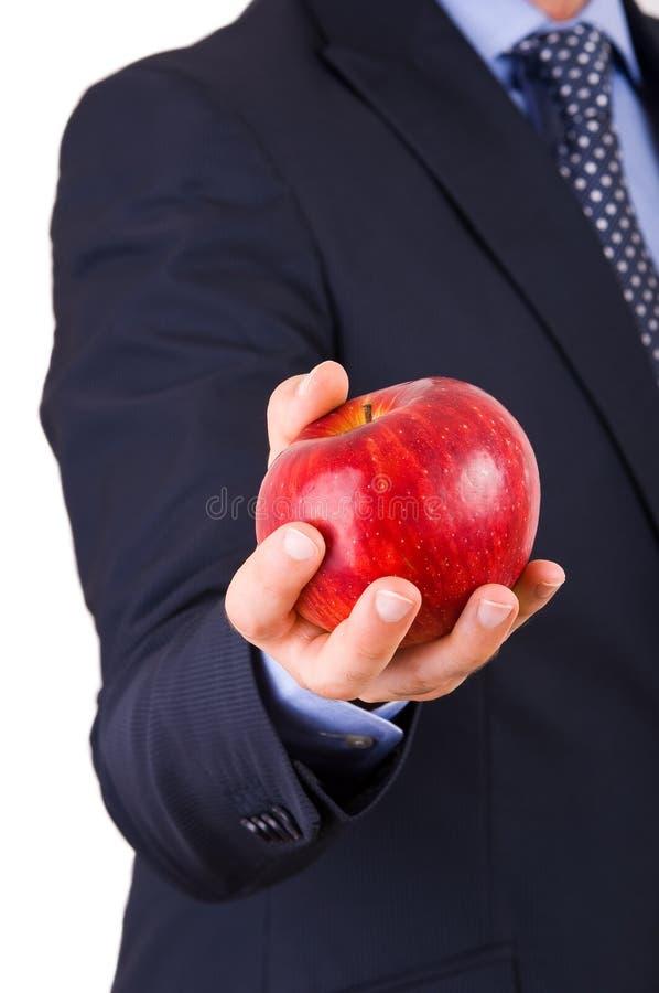 Affärsman som rymmer ett rött äpple. arkivbild
