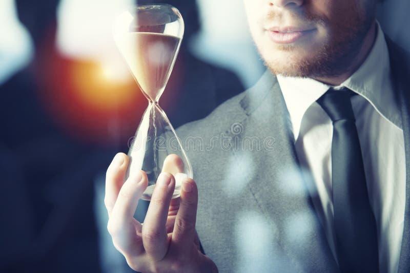 Affärsman som rymmer ett timglas Begrepp av stopptiden i affär royaltyfri foto