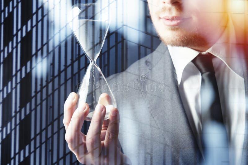 Affärsman som rymmer ett timglas Begrepp av stopptiden i affär arkivbilder
