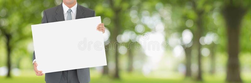 Affärsman som rymmer ett tomt kort mot grön suddig bakgrund fotografering för bildbyråer