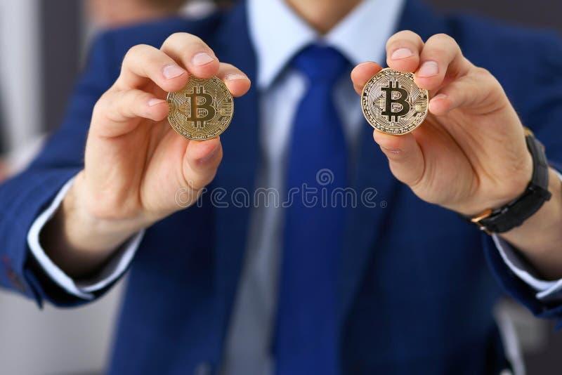 Affärsman som rymmer guld- bitcoin och att le Faktiskt anonymt pengarbegrepp, framgång i digital finans royaltyfria foton